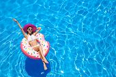 Beautiful young woman with inflatable donut in blue swimming pool poster
