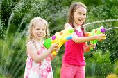 Adorable Little Girls Playing With Water Guns On Hot Summer Day. Cute Children Having Fun With Water poster