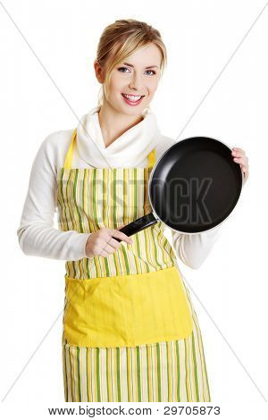 Front view portrait of a young smiling caucasian female teen dressed in apron, holding the frying pan,isolated on white.