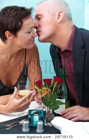 Photo of a mature married couple in a restaurant, he is giving her a kiss on the cheek.