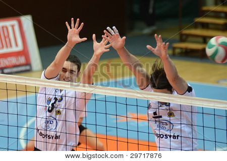 KAPOSVAR, HUNGARY - JANUARY 28: Andras Geiger (R) in action at a Hungarian volleyball National Championship game Kaposvar (white) vs. Sumeg (blue), on January 28, 2012 in Kaposvar, Hungary.