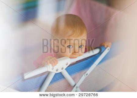 Portrait Of Lonely Baby Standing In Playpen