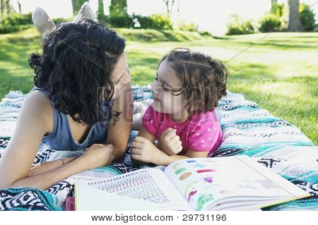Young girl and her mother lying on a lawn looking at each other