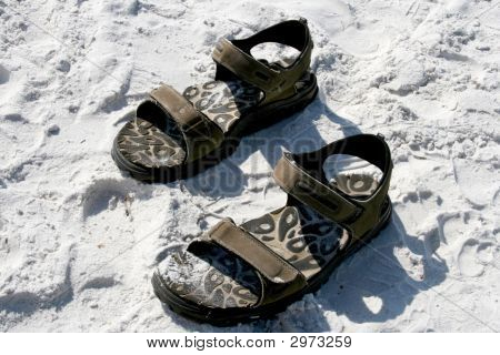 Pair Of Sandles In The Sand At Beach