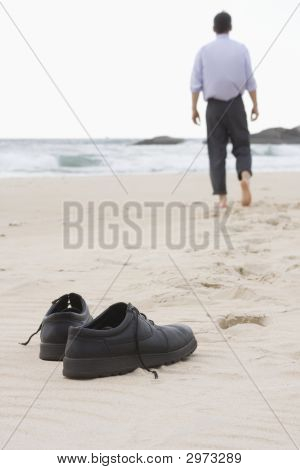 Businessman Walking Barefoot On Beach