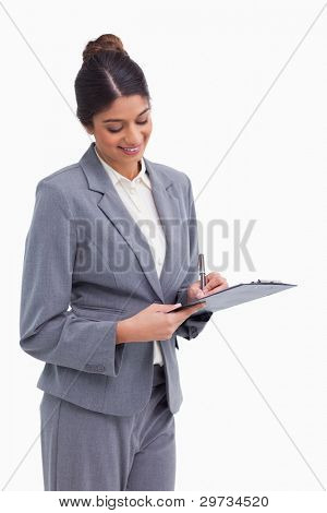 Smiling female entrepreneur taking notes on clipboard against a white background