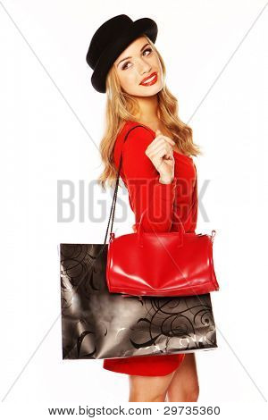 Glamorous blonde woman in a fashionable red ensemble out shopping with a large decorative carrier bag.