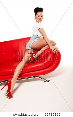 Leggy retro model in stilettos and shorts stretching out on a red leather couch, beauty and fashion