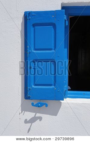 Greek blue shuttered window with shadow