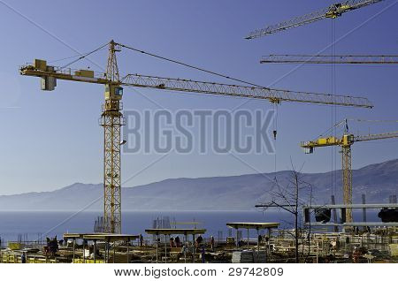 Busy Workers And Cranes At Construction Site