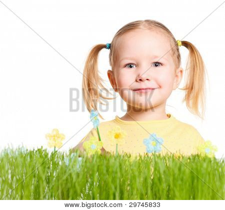 Adorable little girl behind fresh green grass and colorful handmade flowers