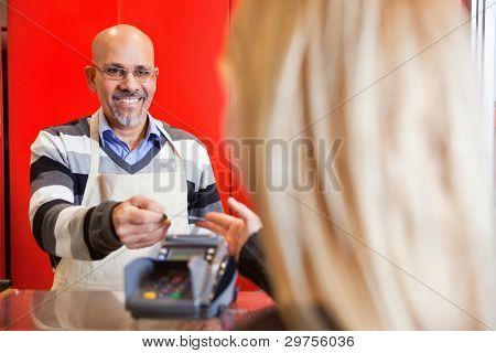 View of woman passing over credit card to shop assistant after shopping