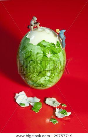 Miniatur-Arbeiter schälen Ei
