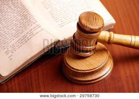 Old book and gavel on wooden desk