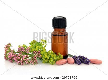 Lavender herb, valerian, ladies mantle flower heads and aromatherapy bottle with alternative medicine pills over white background.