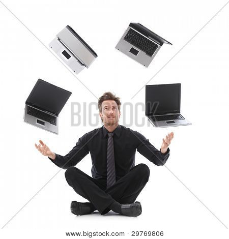 Handsome businessman in tailor seat juggling with laptops.?