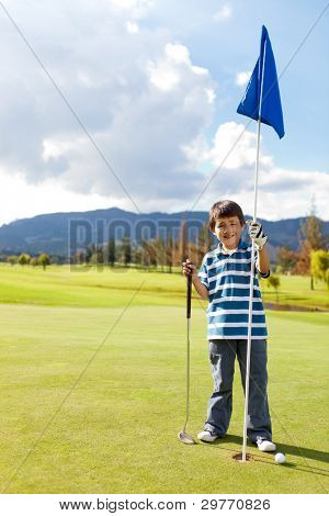 Boy with a golf flag in the hole at the course