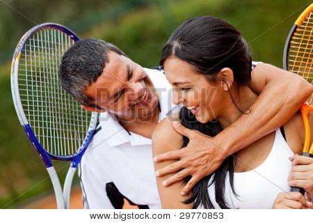 Tennis couple flirting at the court and smiling