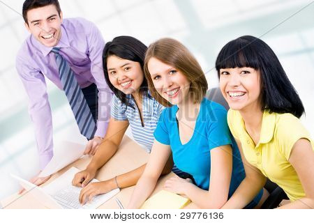 Happy group of young students studying together in a college