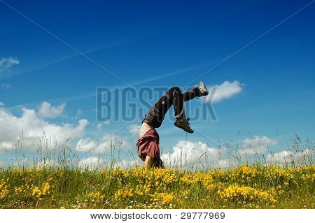 Young woman doing a cartwheel in a meadow