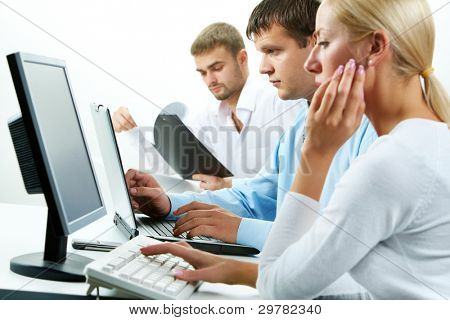 Image of serious business partners typing in working environment