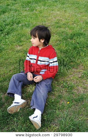 Alone kid boy is sitting on the grass