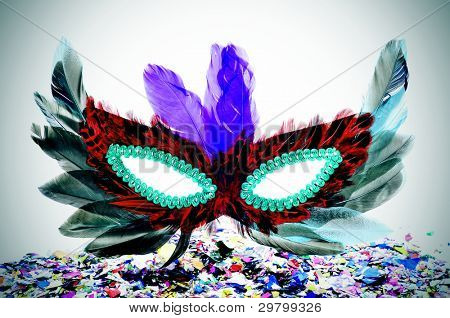 a carnival mask with feathers of different colors and confetti