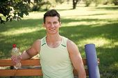 Towards Healthier Lifestyle. Man Smiling Face With Yoga Mat And Water Bottle Sit On Bench In Park. J poster