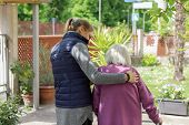 Young Carer Walking With The Elderly Woman In The Garden poster