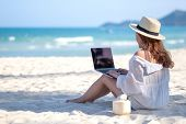 A Woman Using And Typing On Laptop Computer Keyboard While Sitting On A Beautiful Beach poster