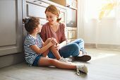 Family Mother And Child Daughter Hugging In Kitchen On Floor poster