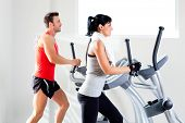 picture of elliptical  - man and woman with elliptical cross trainer in sport fitness gym club - JPG