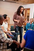 Woman Standing To Address Self Help Therapy Group Meeting In Community Center poster
