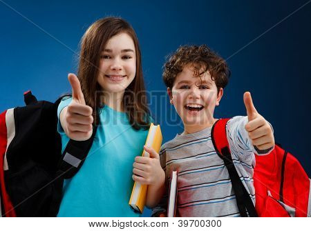 Students holding books showing ok sign