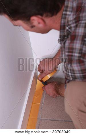 Man taping off wall