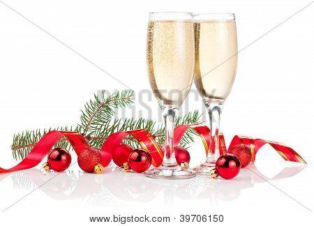Dos Copa de Champagne, cinta roja, bolas de Navidad y rama de árbol de pino aislado sobre fondo blanco