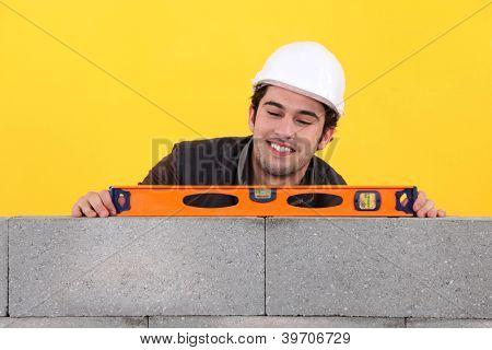 Up-beat mason using spirit-level on wall
