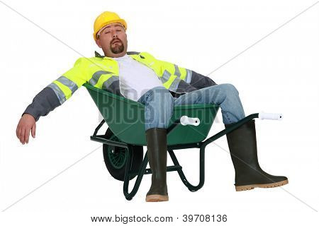 Exhausted builder laying in wheelbarrow