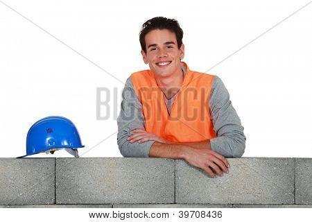 Young mason stood by wall