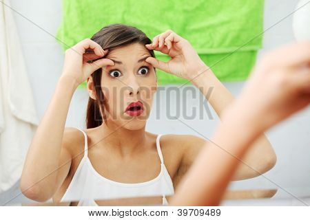 Shocked young woman checking her wrinkles on her forehead at bathroom
