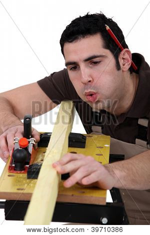 Tradesman blowing shavings off of a wooden plank