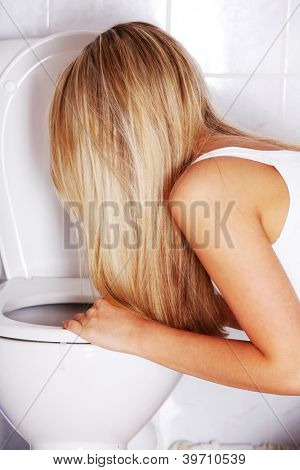 Young blond teen woman vomiting in toilet