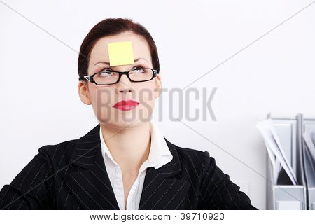 Thinking businesswoman with post it note on her forehead sitting in the office.