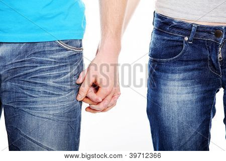 Closeup of young affectionate couple holding hands over white background.