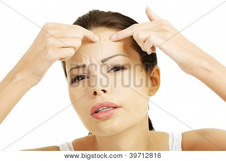 Young woman with pimple on her face. Trying to squeeze it. Isolated on white background.