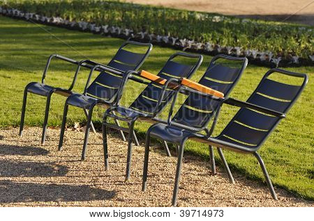 Four Metallic Chairs In A Garden