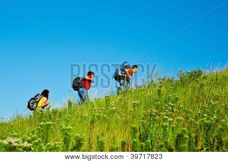 Fellow high school students with backpacks moving up the hill