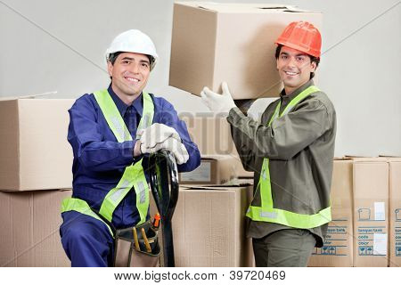 Two happy foremen loading cardboard boxes at warehouse