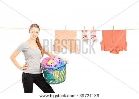 Smiling woman holding a laundry basket and a laundry line with clothes isolated on white background