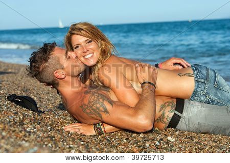 Sexy Couple Laying On Pebble Beach.